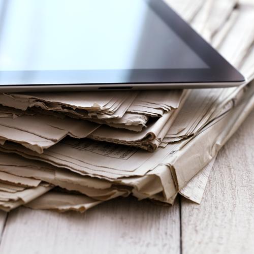 Une tablette posée sur des journaux